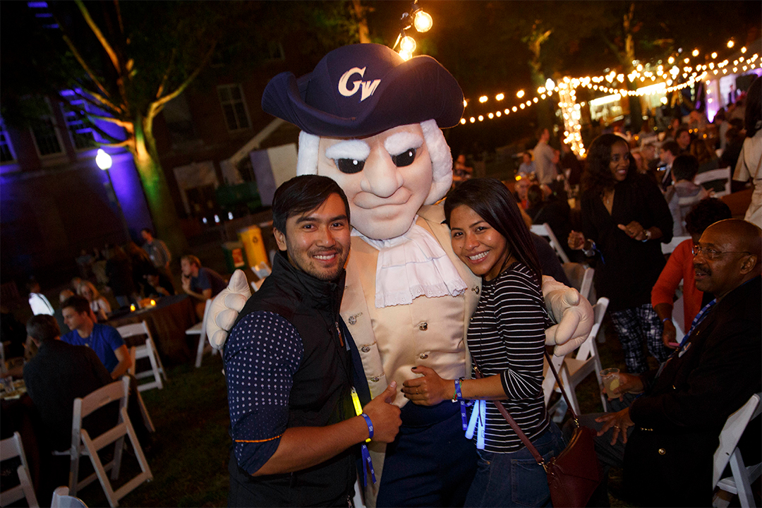 Two students posing with George mascot