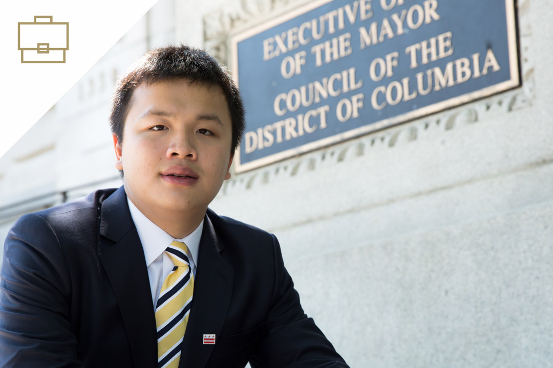 student in a suit in front of building sign Executive Office of the Mayor Council of the District of Columbia