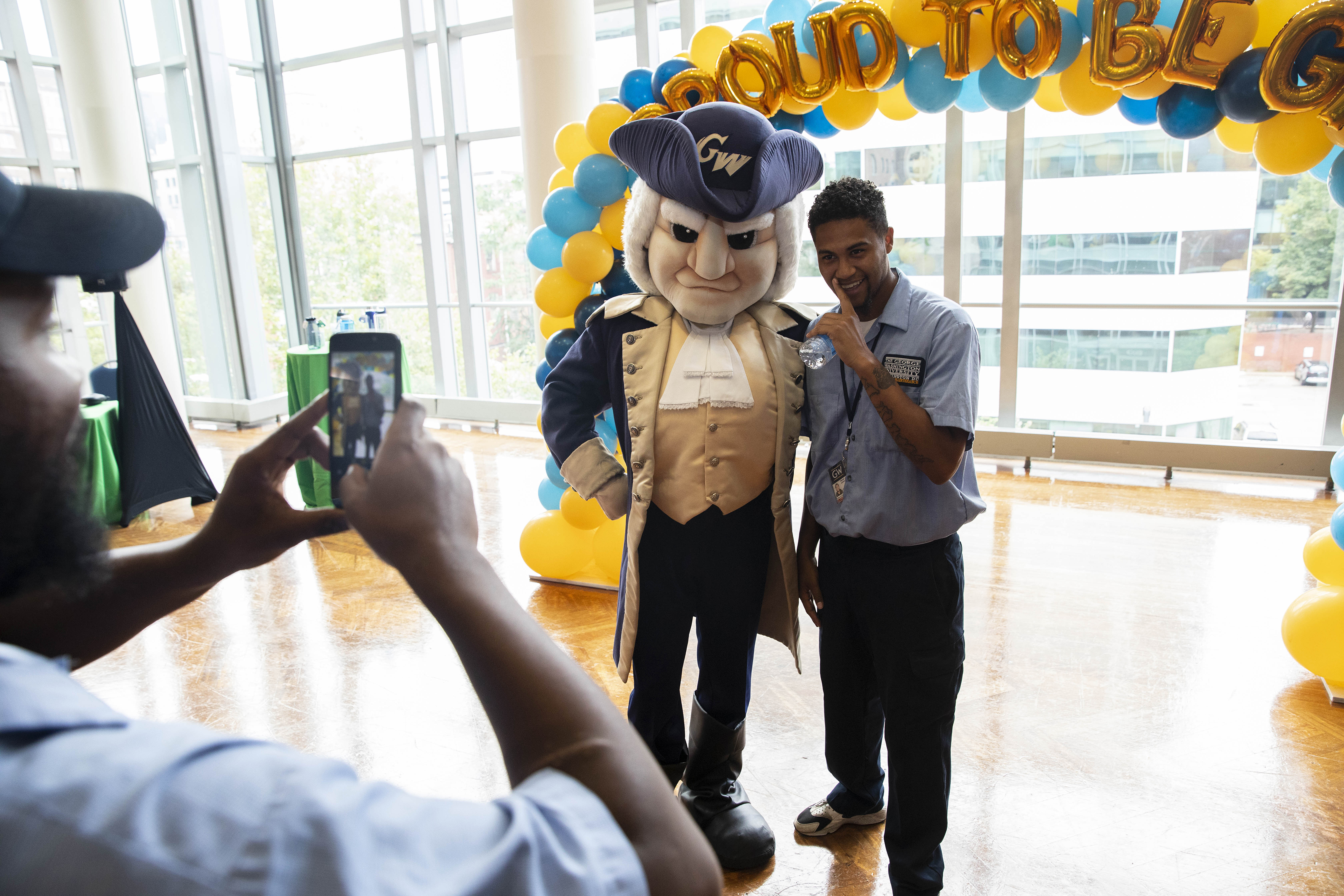Male staff member posing with George mascot under balloon arrangement Proud to Be GW