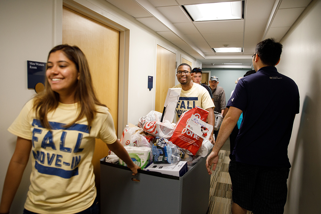 Students with a cart moving into a residence hall