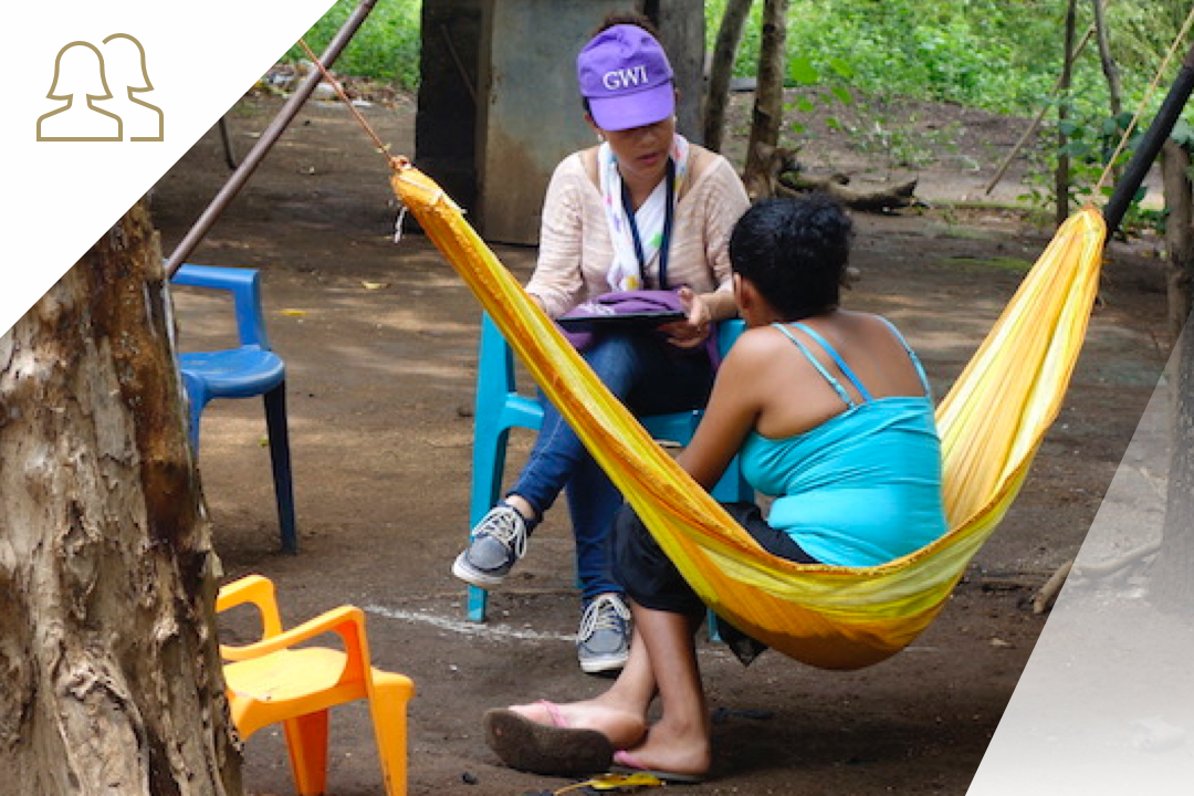 GWI researcher speaking with woman sitting in a hammock