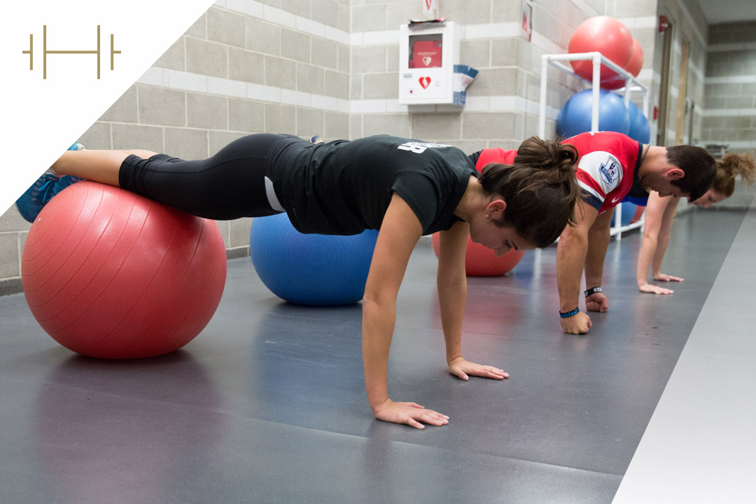 Students doing pushups on exercise balls