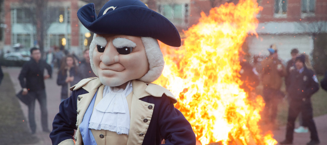 George mascot standing in front of bonfire
